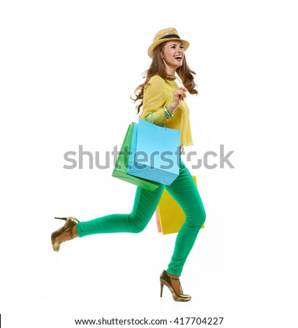Colourful shopping vibes. Full length portraits of smiling brunette woman in hat and bright clothes with shopping bags running - stock photo