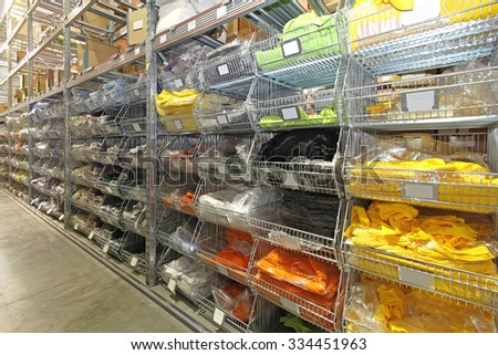 Colourful T Shirts and Textile Goods in Warehouse Wire Rack - stock photo