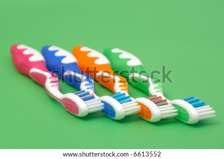 colourful toothbrushes on green background - stock photo
