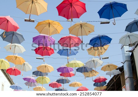 Colourful umbrellas danging over the top of a bazaar street popular for its restaurants and cafes in the historic district of Antalya, Turkey. - stock photo