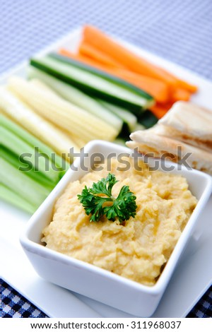 Colourful vegetarian platter of raw carrots, corn, cucumber and celery sticks with chickpea dip and flat bread  - stock photo