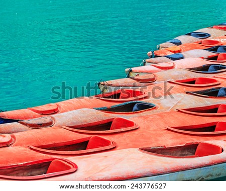 Colourful yellow and red kayaks on turquoise sea water background - stock photo