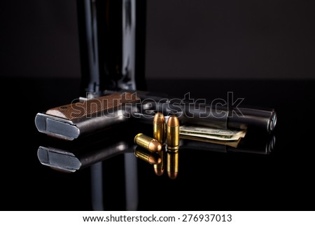 Colt 1911 with ammunition and money on black - stock photo