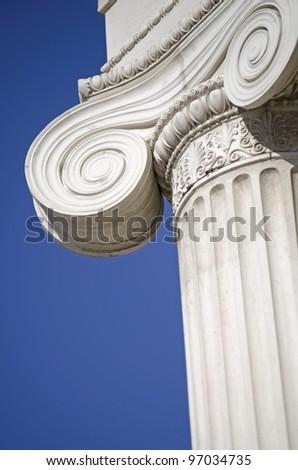 column of white stone detail on blue background - stock photo