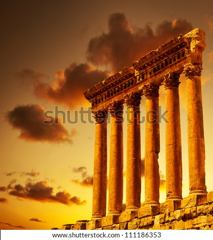 Column ruins over sunset, ancient lebanese building, Heliopolis Baalbek columns in Lebanon, arabian aged landmark, famous temple monument, travel, vacation, tourism concepts - stock photo