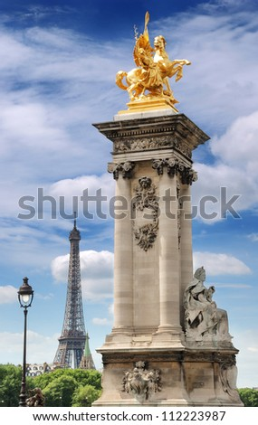 Column with gilded sculpture on the Pont Alexandre III bridge and Eiffel Tower in Paris, France. - stock photo