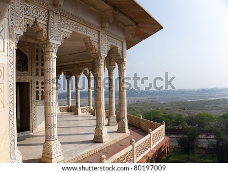 Columned viewing point outside royal chambers at Agra Fort Palace in India. Wide view over Yumana river and surrounding land out of decorated marble patio. - stock photo