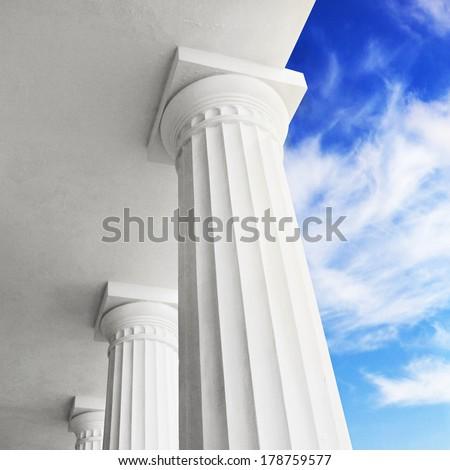 Columns on blue sky background. - stock photo