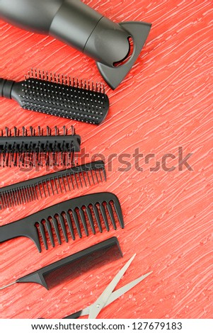 Comb brushes, hairdryer and cutting shears,on color background - stock photo