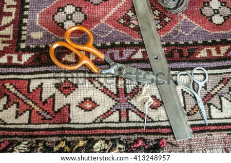 Comb,scissors,needle and woolen thread for the restoration of the old  woolen carpet - stock photo