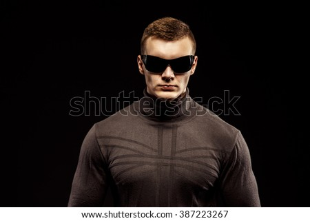 Combat muscled action hero man wearing brown sweater and sunglasses. Studio shot. - stock photo