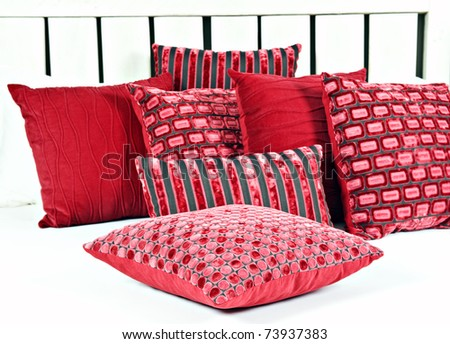 Combination of red and brown pillows on a bed with white linen - stock photo