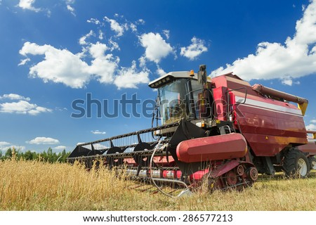 Combine harvester at the edge of grain field during hot harvest time - stock photo