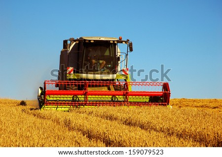 Combine harvester at work harvesting a field of wheat - stock photo