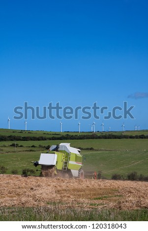 Combine harvester in a feild below wind turbines Isle of Anglesey - stock photo