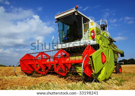 combine harvester in field. large farm machine in bright green and red. agricultural equipment for harvesting crop - stock photo