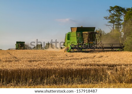 Combine harvesters working on the field , collecting harvest is abundant. - stock photo