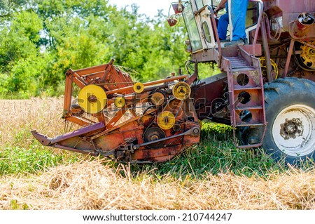 Combine harvesting mature wheat crops - stock photo