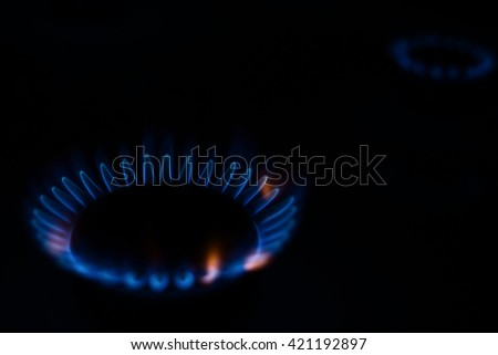 combustion gas in the dark on a hob - stock photo