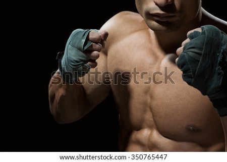Come at me. Cropped shot of a boxer standing ready to fight on black background - stock photo