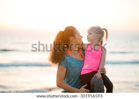 Come here and give me a little kiss. A mother lovingly leans in to her young daughter. The mother is kneeling next to her daughter and holding her close. The sun is going down on another lovely day. - stock photo