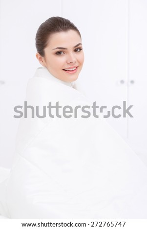Comfort and convenience. Young smiling lady having fun covered with white warm blanket on white background in morning - stock photo