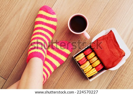 Comfort Concept - Woman drinking hot cocoa and eating delicious macaroon. Close-up of female legs in bright colored warm socks with a retro vintage instagram filter. - stock photo