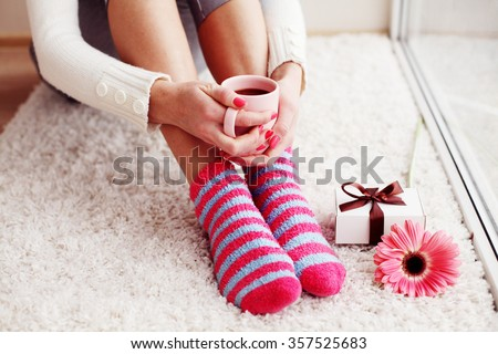 Comfort Concept - Woman drinking hot cocoa. Close-up of female legs in bright colored warm socks with a retro vintage instagram filter. - stock photo