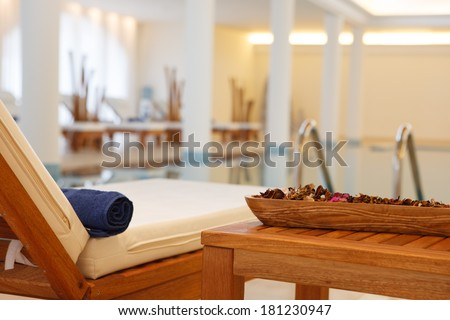 Comfortable adjustable wooden recliner seat with a foam cushion and attached side table standing poolside at an indoor swimming pool at a resort or spa - stock photo