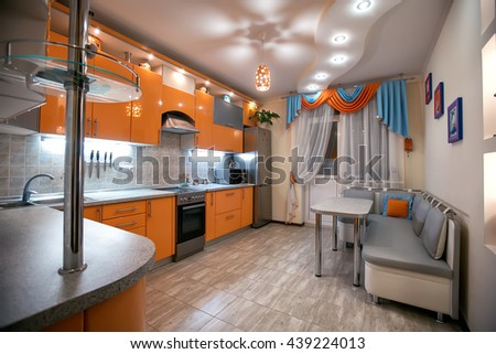 Comfortable apartment in the orange and blue tones. Kitchen with dining room. interior, flat, design, architectural design, style, color, yellow, suspended ceilings, floor tiles - stock photo