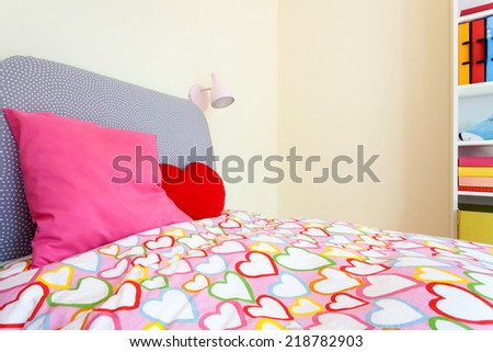 Comfortable bed with colorful bedding in little girl room - stock photo