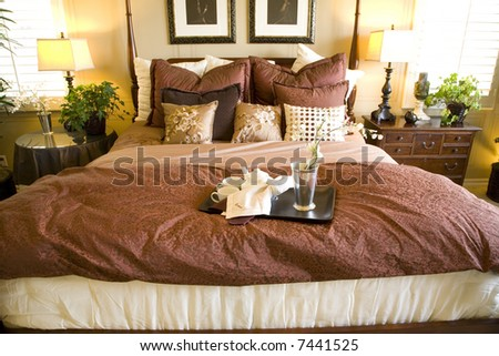 Comfortable bedroom with bed close-up and modern decor. - stock photo