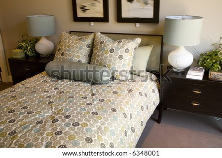 Comfortable bedroom with bed closeup and modern decor. - stock photo