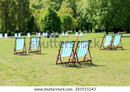 Comfortable deck chair inviting people to relax on summer day in beautiful St. James park, London, UK - stock photo