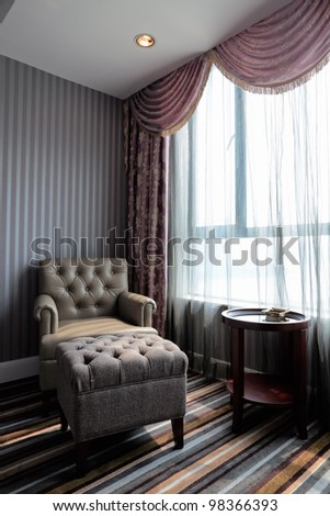 comfortable hotel room corner, leather chair and tea table by the window - stock photo