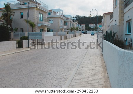 Comfortable light street with pavement, trees, cars and the same neat white houses covered with red tile, Protaras in Cyprus - stock photo