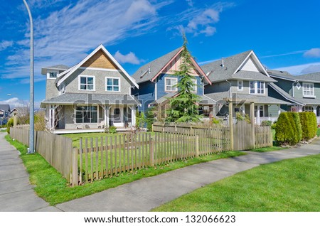 Comfortable neighborhood. Some middle class homes with nicely landscaped front yard lawn behind the wooden fence in the suburbs of the North America. Canada. - stock photo
