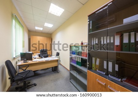 Comfortable office room with bookshelf and folders - stock photo