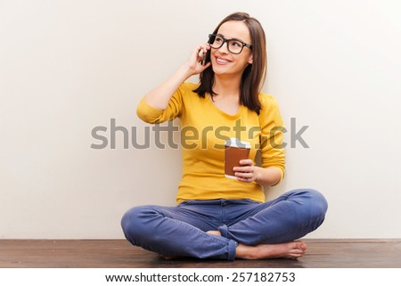 Comfortable place for the rest. Beautiful young woman in eyewear holding mobile phone and a cup of coffee while sitting on the floor against brown background - stock photo