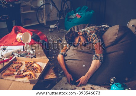 Comfortable place to pass out. Young handsome man passed out on bean bag with joystick in his hand in messy room after party - stock photo