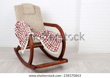 Comfortable rocking-chair with rug on wooden floor near the brick wall background - stock photo