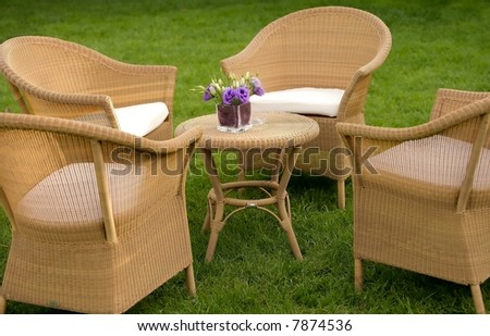 Comfortable setting of straw sofas and table in a garden - stock photo