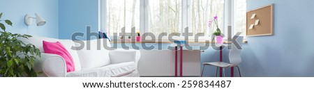 Comfortable white couch in stylish blue children room - stock photo