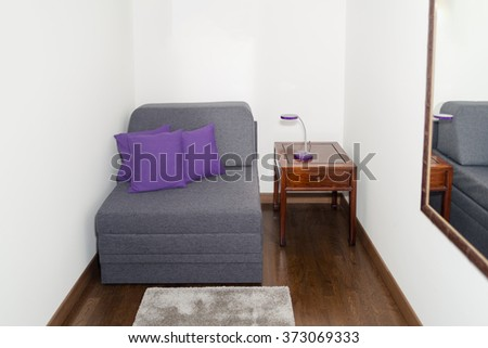 Comfy Gray Armchair with Purple Pillow near a Small Table with Modern Night Lamp. Armchair in a Small Room for Guests Rest with Mirror on the Wall - stock photo