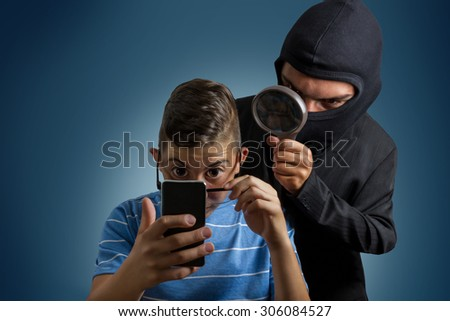 comic masked man spying data from smartphone of teenager - stock photo