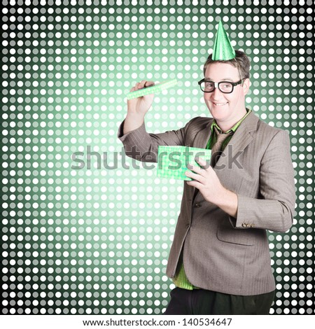 Comic portrait of a dorky dad opening father day gift box with smile on green dotted background. Celebrations and events - stock photo