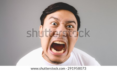 Commanding loudly at the camera. An asian man with white t-shirt and grey background. - stock photo