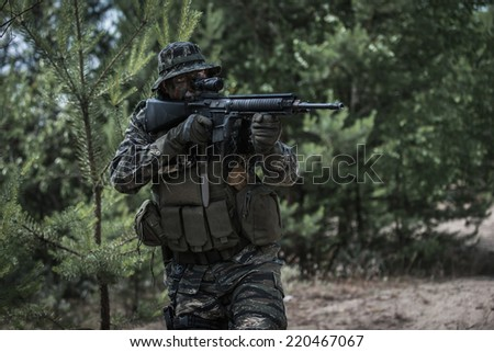 Commando aiming with assault rifle at enemy target - stock photo