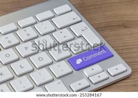 Comment and speech bubbles on a large blue button of a modern keyboard on a wooden desktop - stock photo
