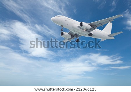 Commercial airliner before landing flying above with blue sky in background - stock photo
